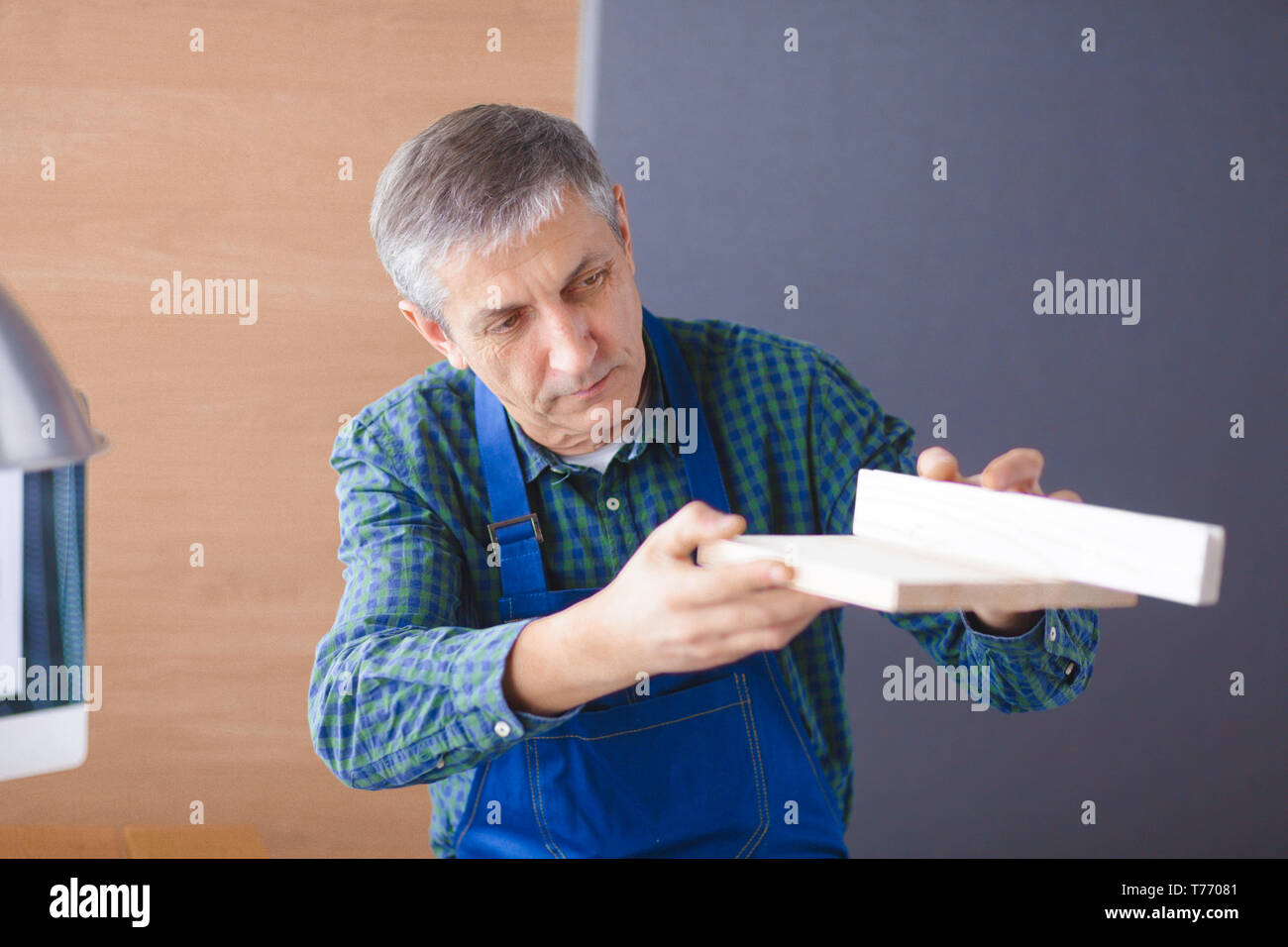 profession, carpentry, woodwork and people concept - carpenter testing wood plank evenness at workshop. - Stock Image