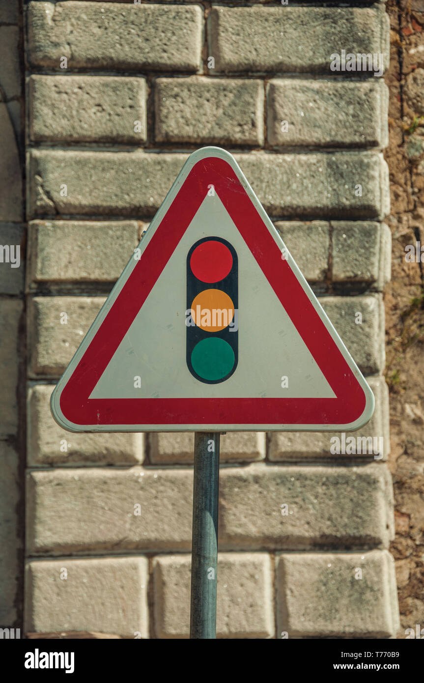 Close-up of TRAFFIC SIGNAL AHEAD road sign in front of stone brick wall at Elvas. A gracious city on the easternmost frontier of Portugal. - Stock Image