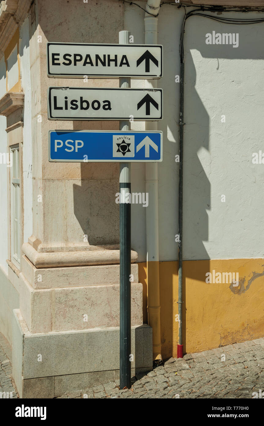 Signpost in a deserted street indicating the Police and city directions at Elvas. A gracious city on the easternmost frontier of Portugal. - Stock Image
