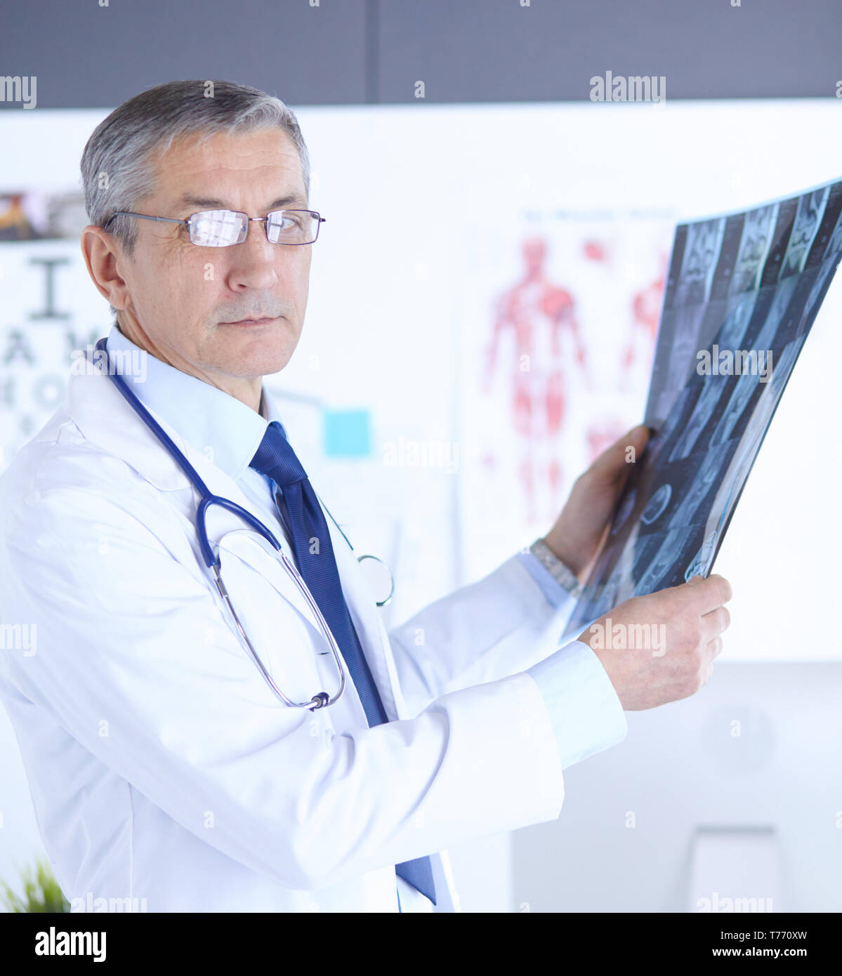 Doctor in the office examines the patient's x-ray. - Stock Image
