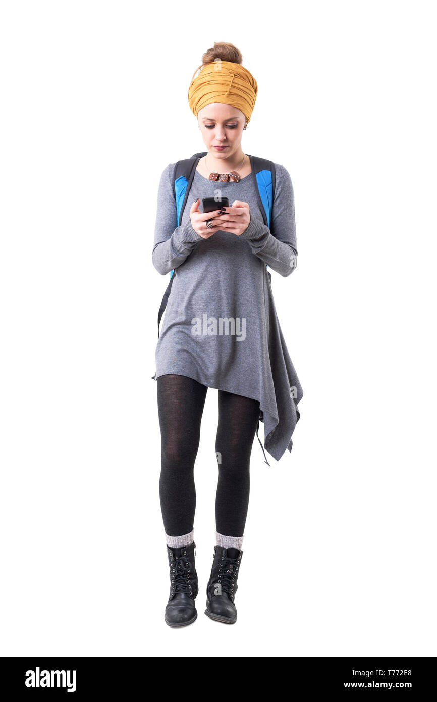 Young tourist hipster woman walking and looking at mobile phone map navigation. Full body isolated on white background. Stock Photo