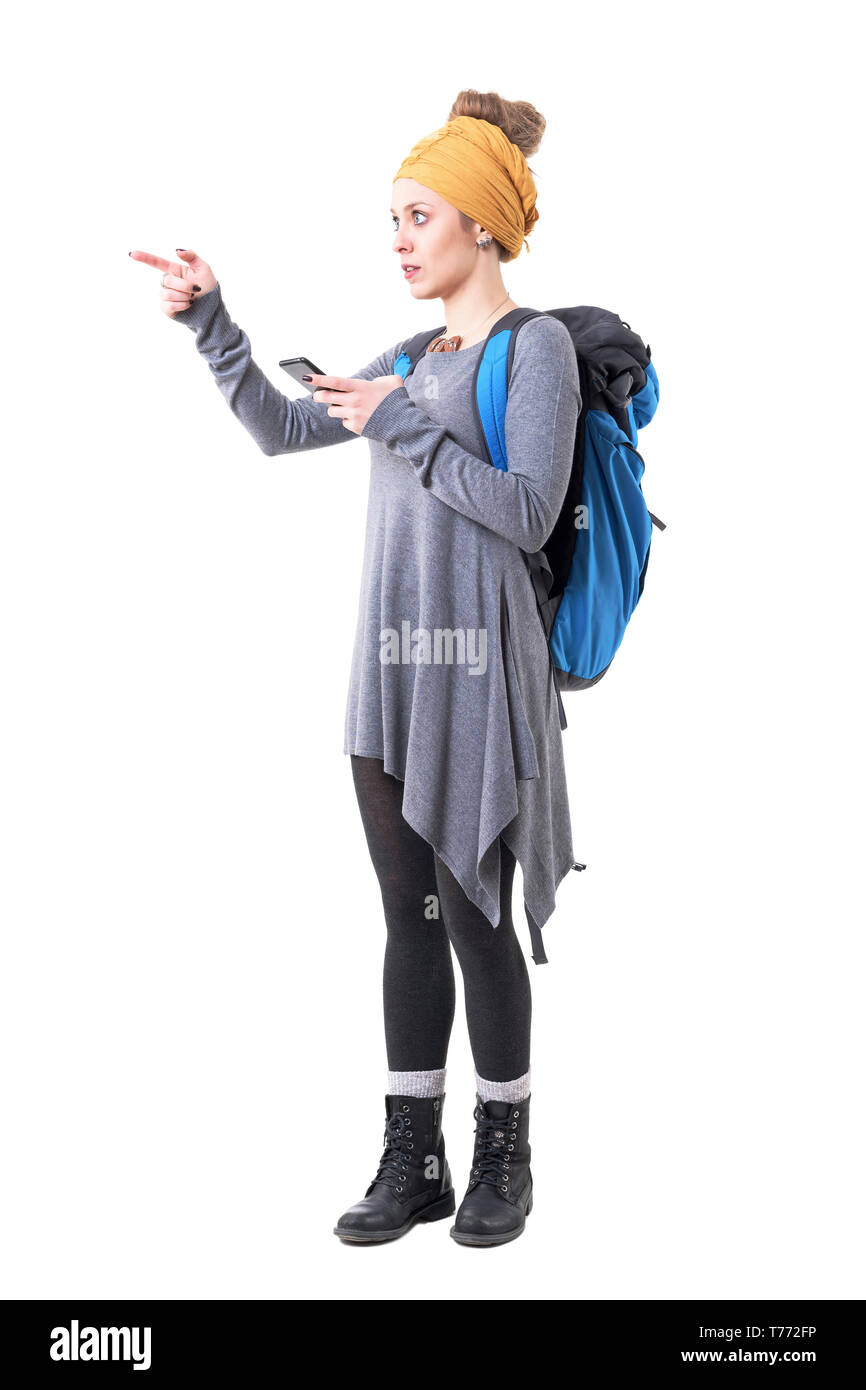 Young confused hipster girl with backpack showing directions using smart phone navigation map. Full body isolated on white background. - Stock Image