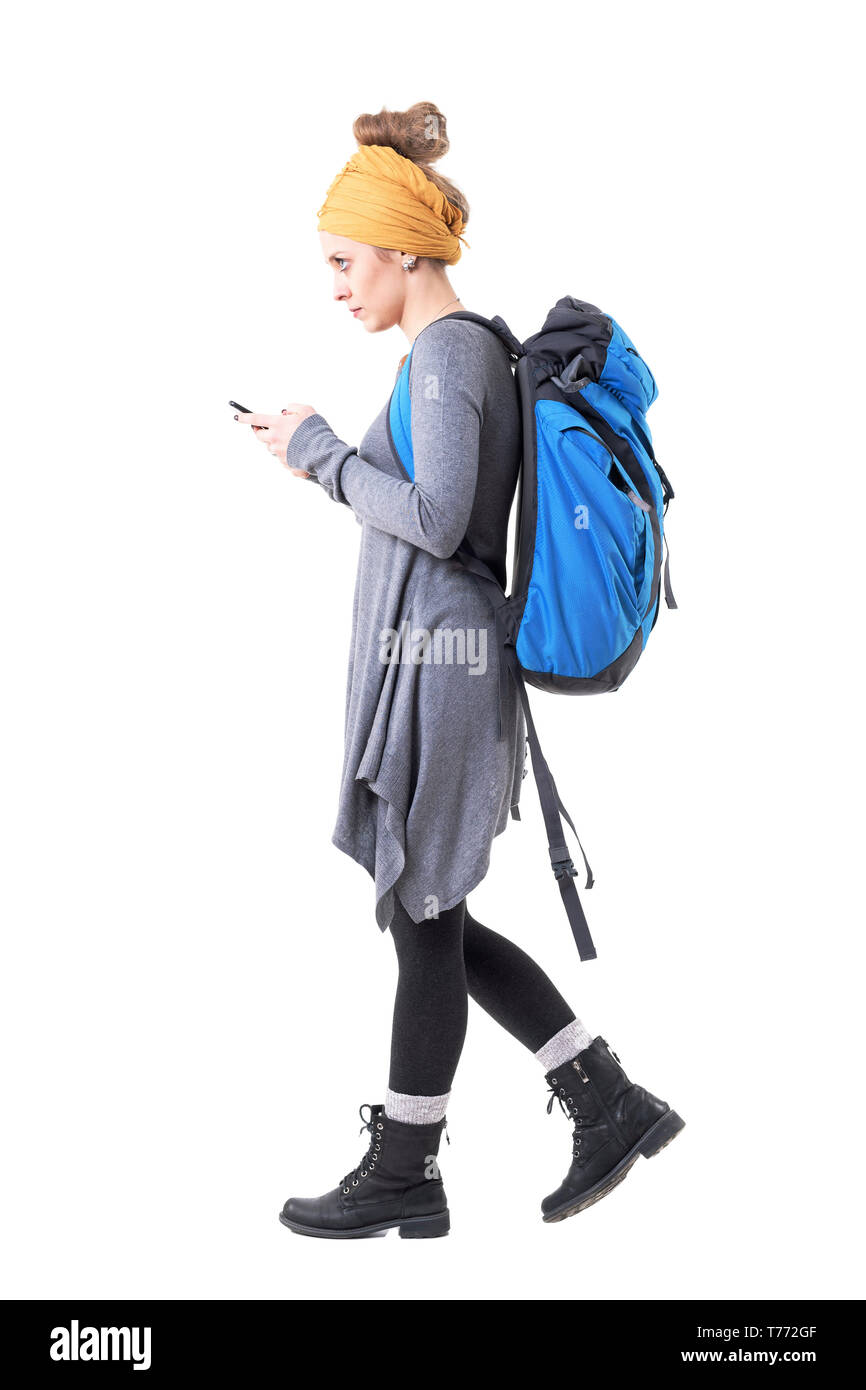 Side view of hipster woman backpacker walking and looking for navigation map on mobile phone. Full body isolated on white background. - Stock Image