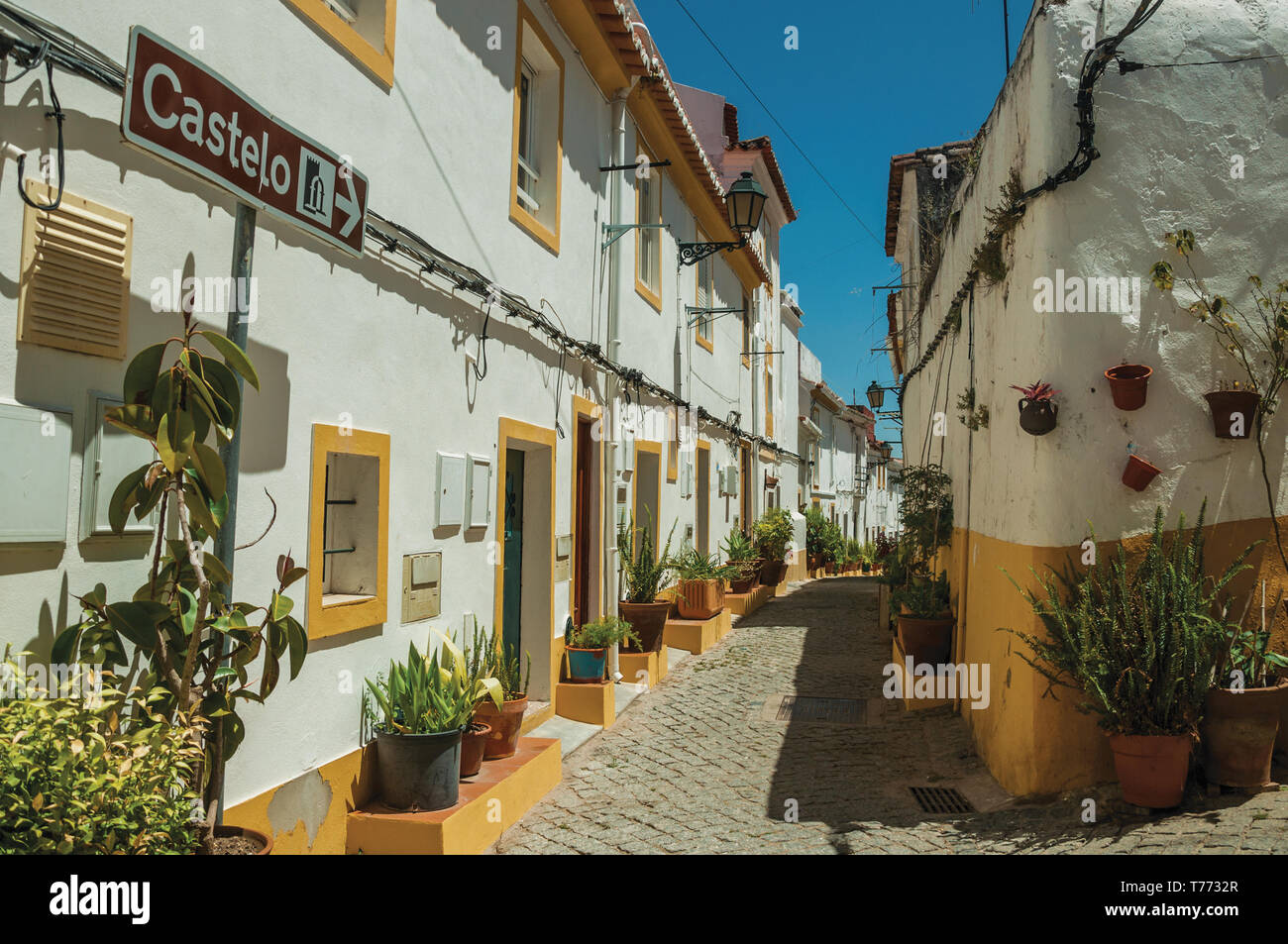 Old colorful houses and signpost indicating the Castle in a narrow alley at Elvas. A gracious city on the easternmost frontier of Portugal. - Stock Image