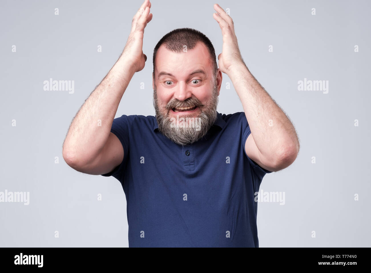 Mature man in blue t-shirt expressive gesticulating with hands, trying to prove his opinion. - Stock Image