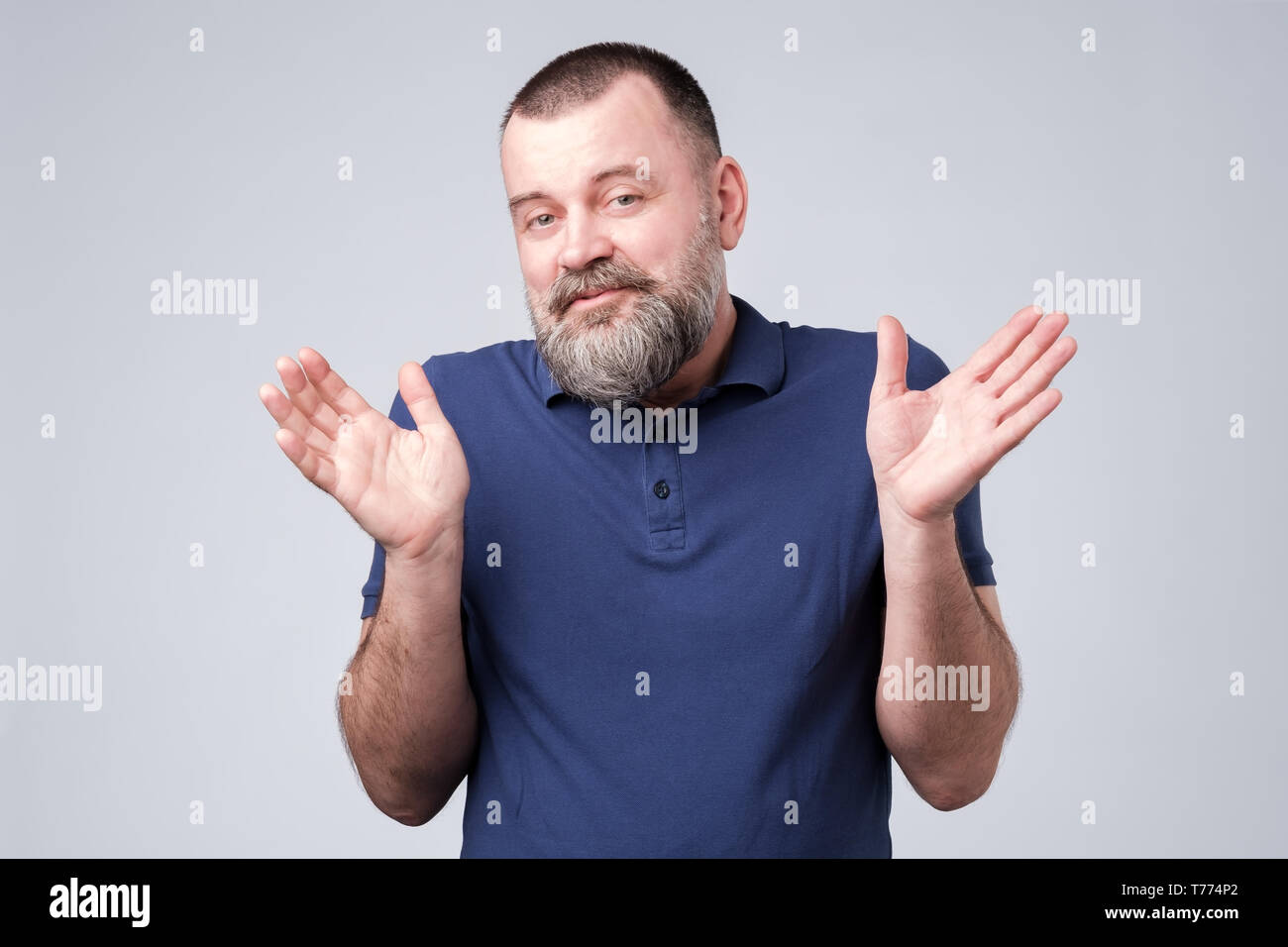 Bearded man in blue t-shirt shrugging shoulders - Stock Image