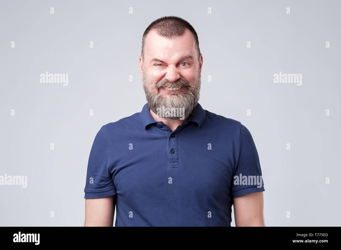 Mature male making a funny smiling grimace. Studio shot - Stock Image