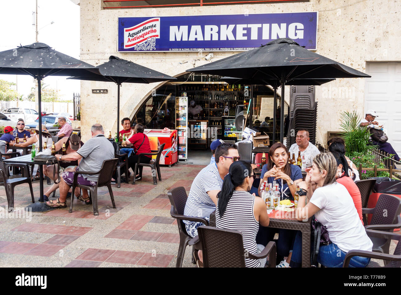 Cartagena Colombia El Laguito beach cafe restaurant tables umbrellas Hispanic resident residents man woman Stock Photo