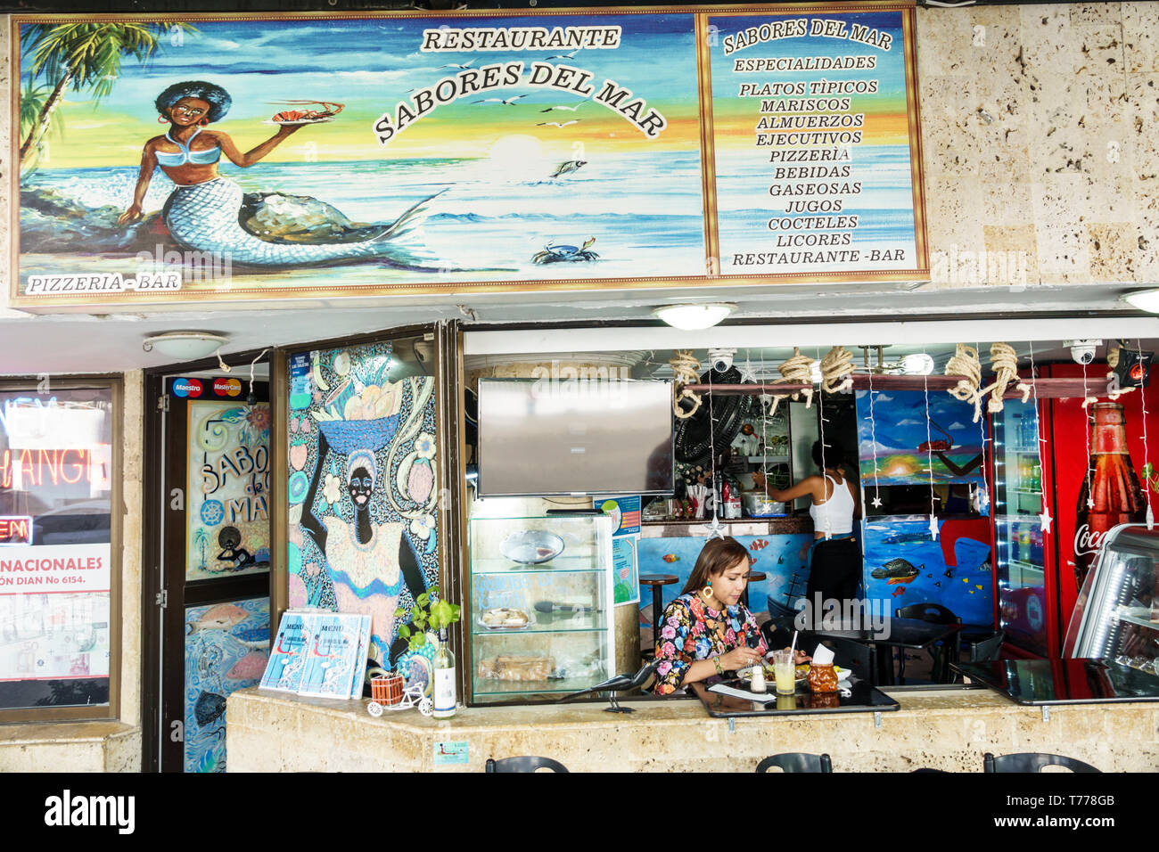 Cartagena Colombia El Laguito restaurant neighborhood family business Sabores del Mar typical food Hispanic resident residents woman eating black merm Stock Photo