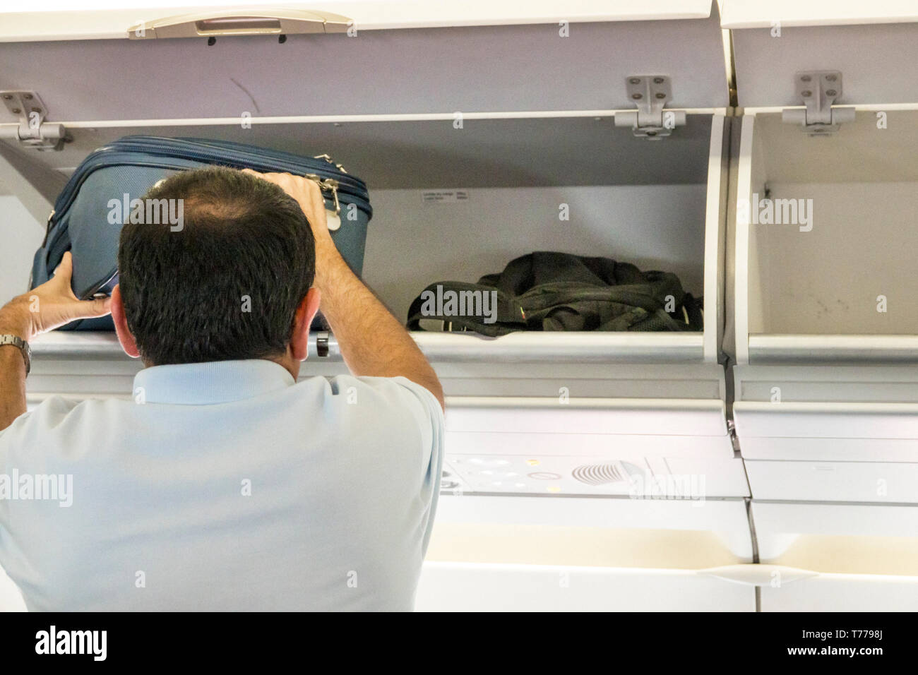 Cartagena Colombia Rafael Nunez International Airport CTG Avianca flight AV 34 onboard cabin Hispanic overhead luggage bin man storing bag - Stock Image