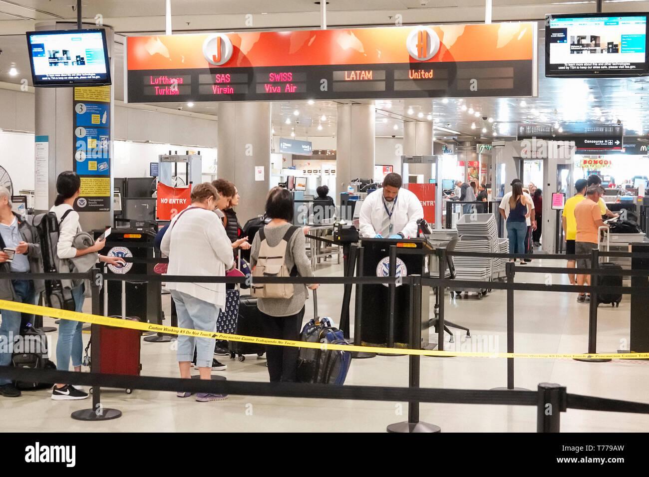 Miami Florida Miami International Airport MIA terminal TSA Department of Homeland Security passenger screening checkpoint agent man woman - Stock Image
