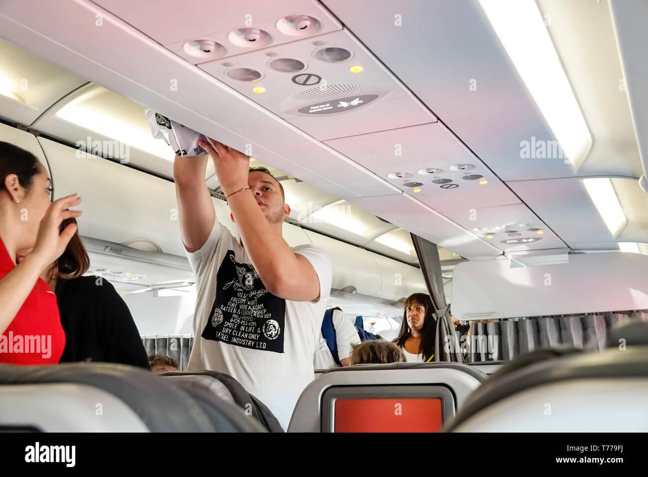 Miami Florida Miami International Airport MIA onboard cabin Avianca Airlines flight AV 35 man storing luggage overhead bin - Stock Image