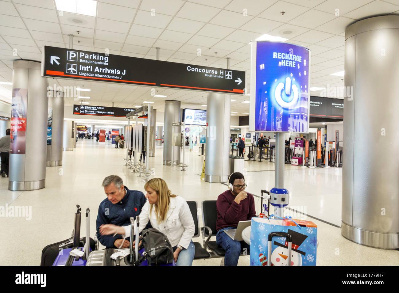 Miami Florida Miami International Airport MIA inside terminal passengers seating recharge kiosk Black man - Stock Image