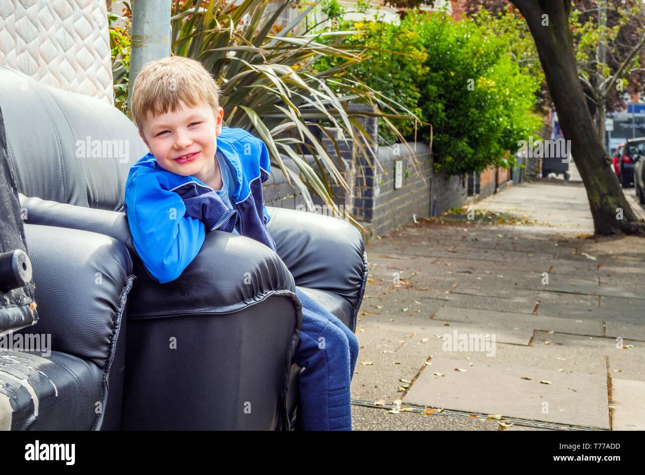 cute child on dumped sofa sitting on british street in training kit. - Stock Image
