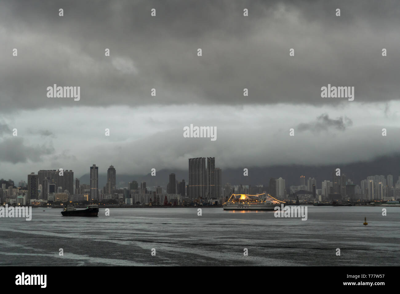 Hong Kong, China - March 7, 2019: Very early morning under dark rainy sky. Kowloon Bay, skyline with tall buildings and couple of ships, one decorated - Stock Image