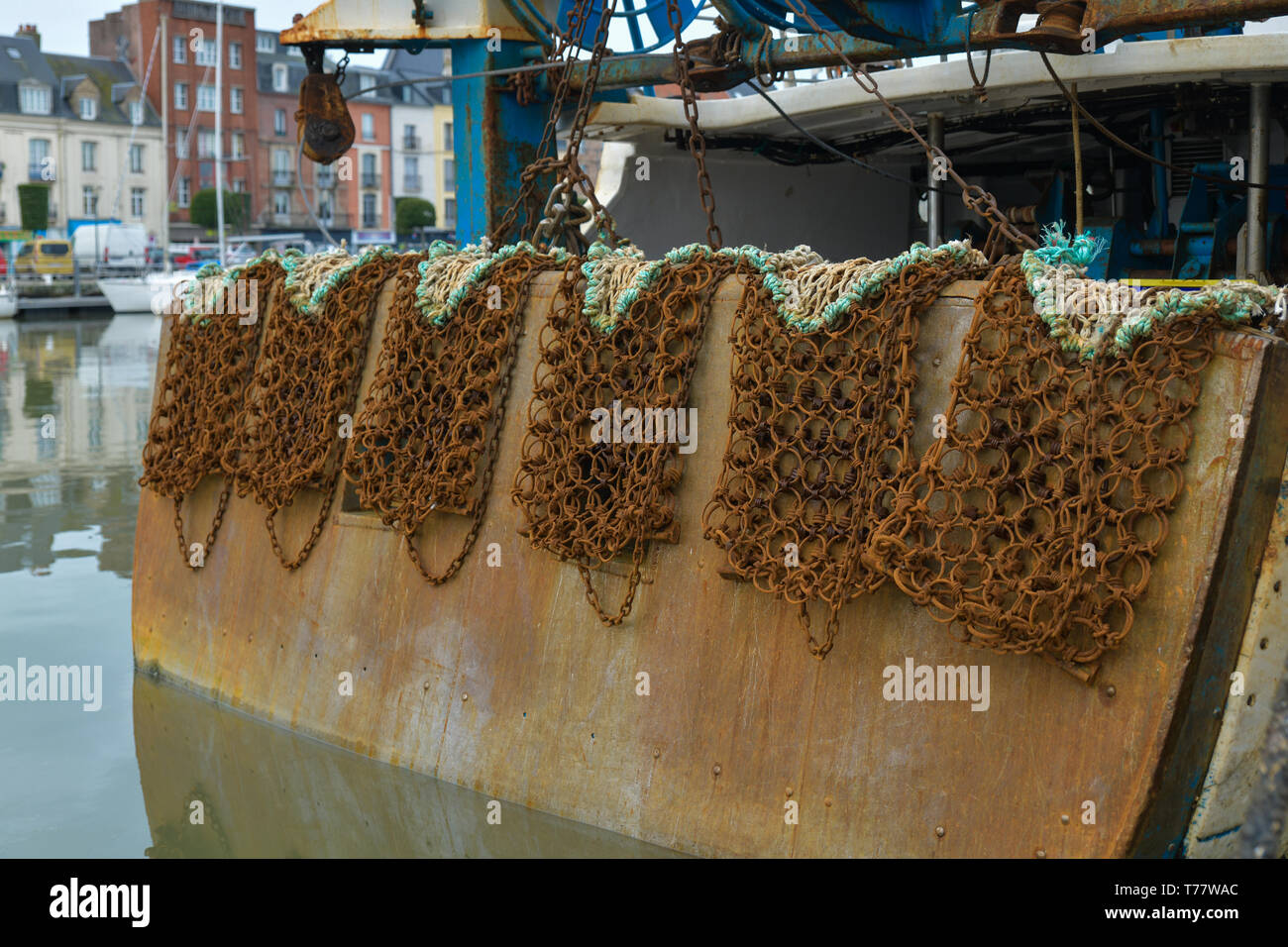 Rusty nets for catching scallops hang on a boat - Stock Image