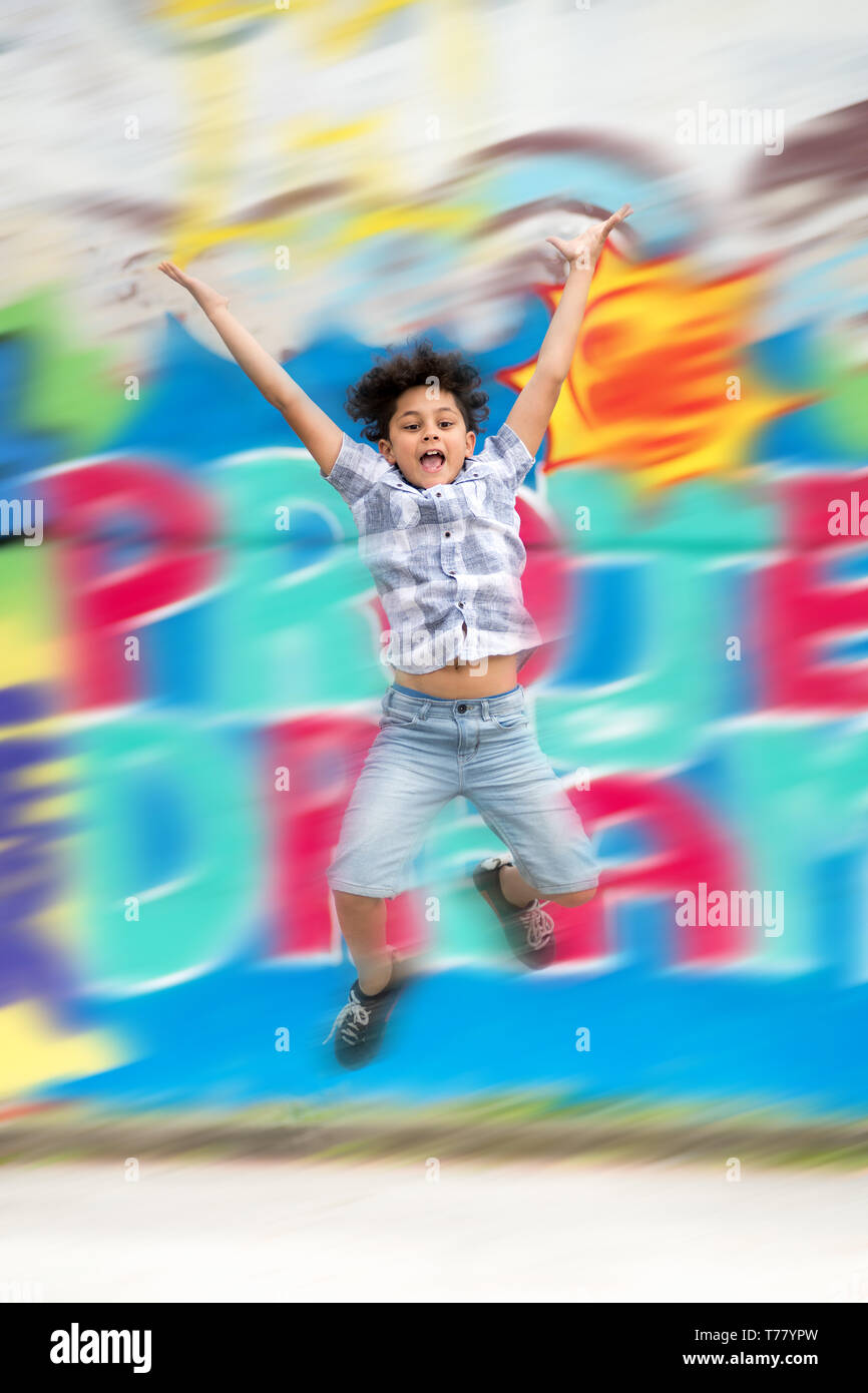 Young boy having fun jumping in the air with arms raised in front of a brightly colored wall with motion blur - Stock Image