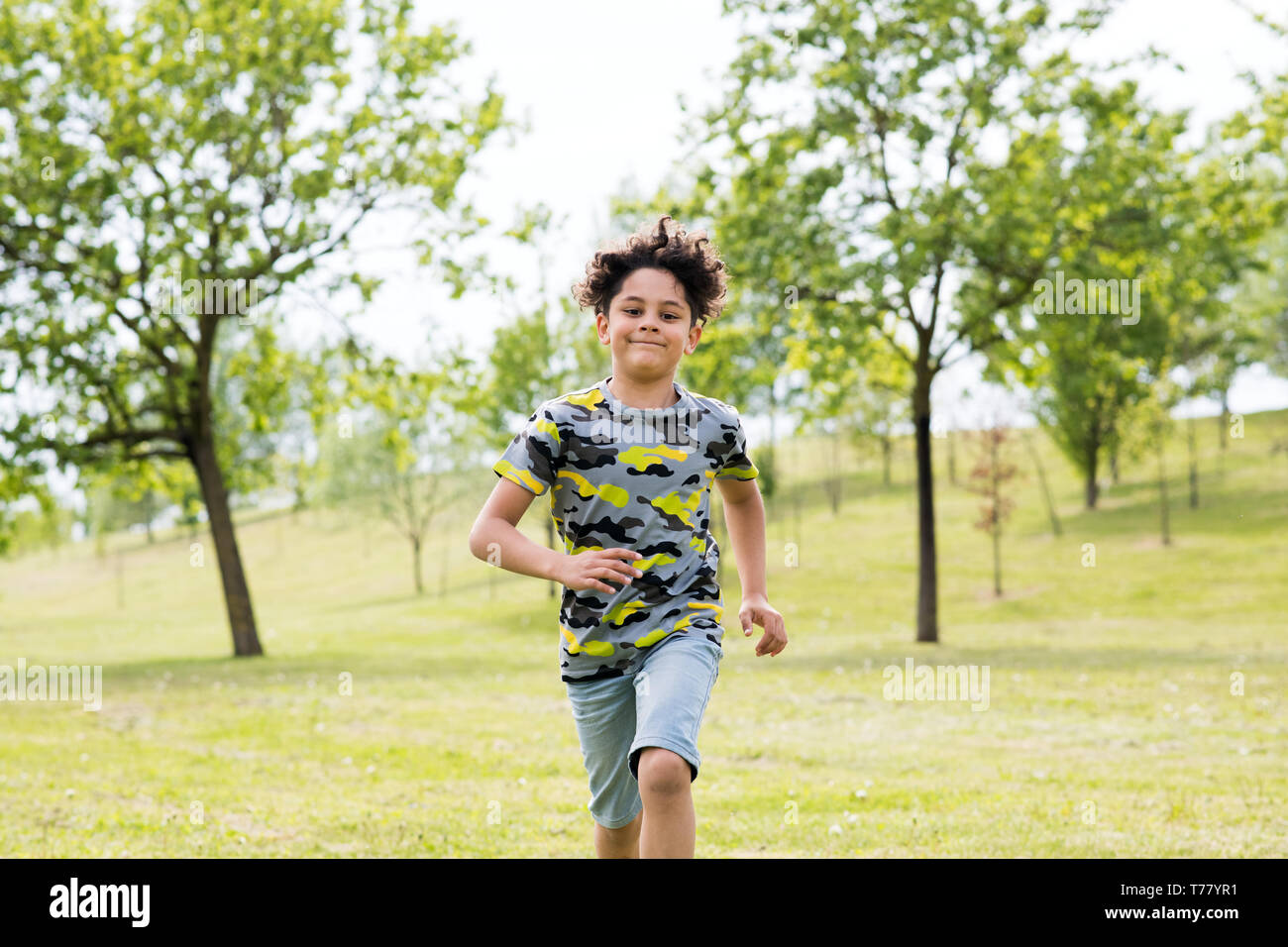 Happy fit young boy running towards the camera across the green grass in a spring garden with a big friendly smile - Stock Image