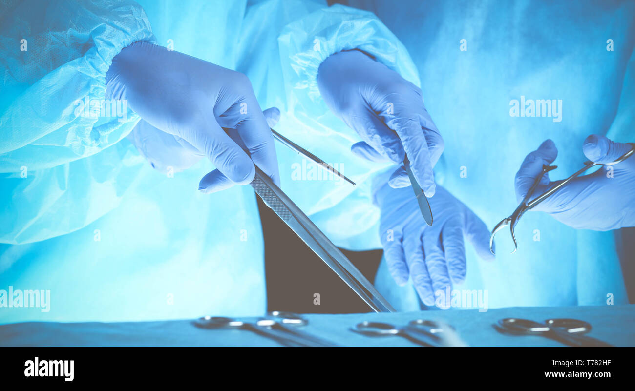 Group of surgeons at work while operating at hospital, close-up of hands. Health care and veterinary concept. - Stock Image