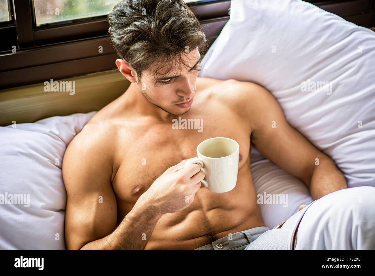Sexy handsome young man laying shirtless on his bed next to window, holding a coffee or tea cup while reading a book Stock Photo