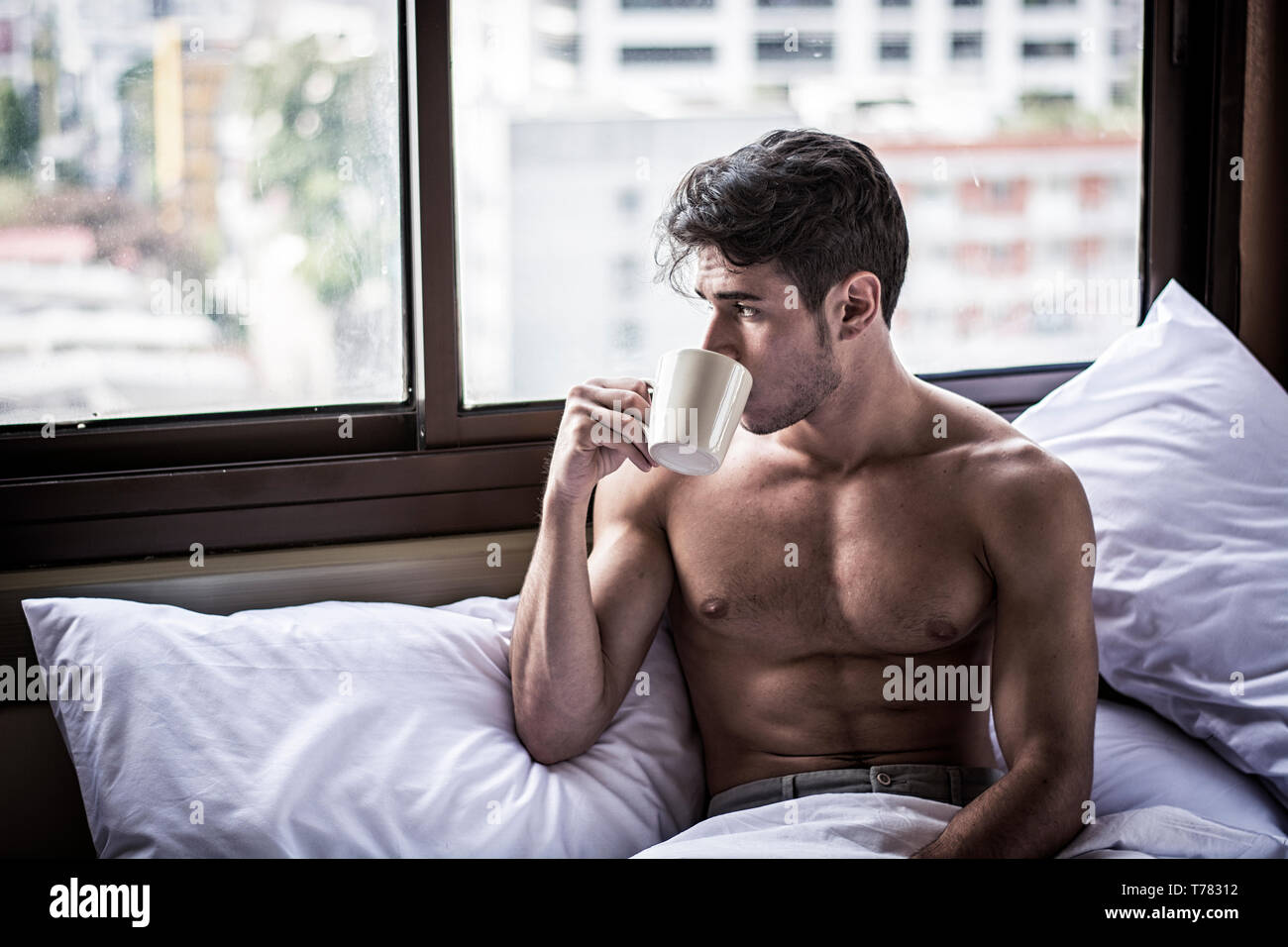 Naked young man with muscular body on bed with mug or cup in hand with coffee or tea Stock Photo
