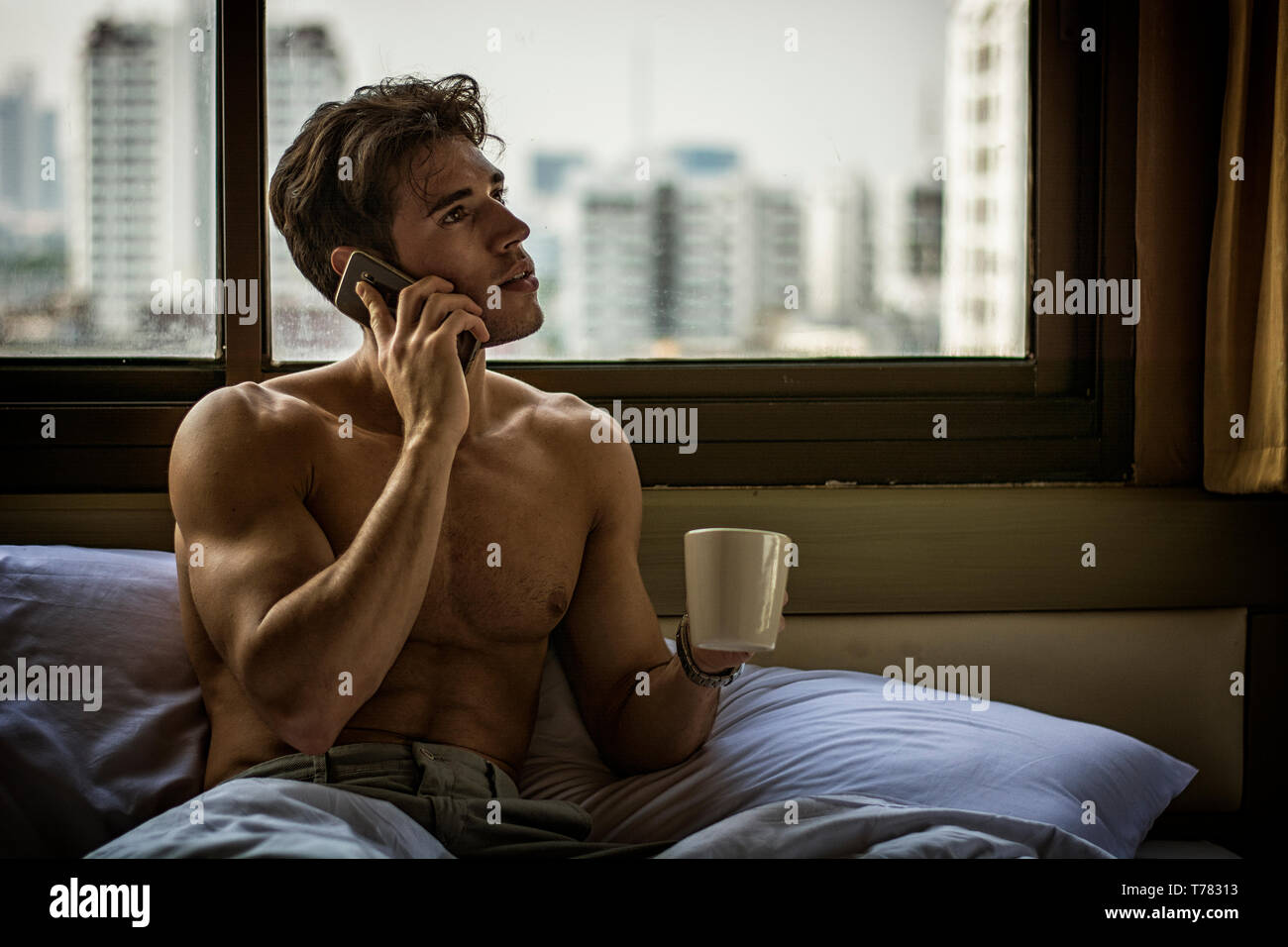 Naked young man with muscular body on bed with mug or cup in hand with coffee or tea talking on cell phone Stock Photo