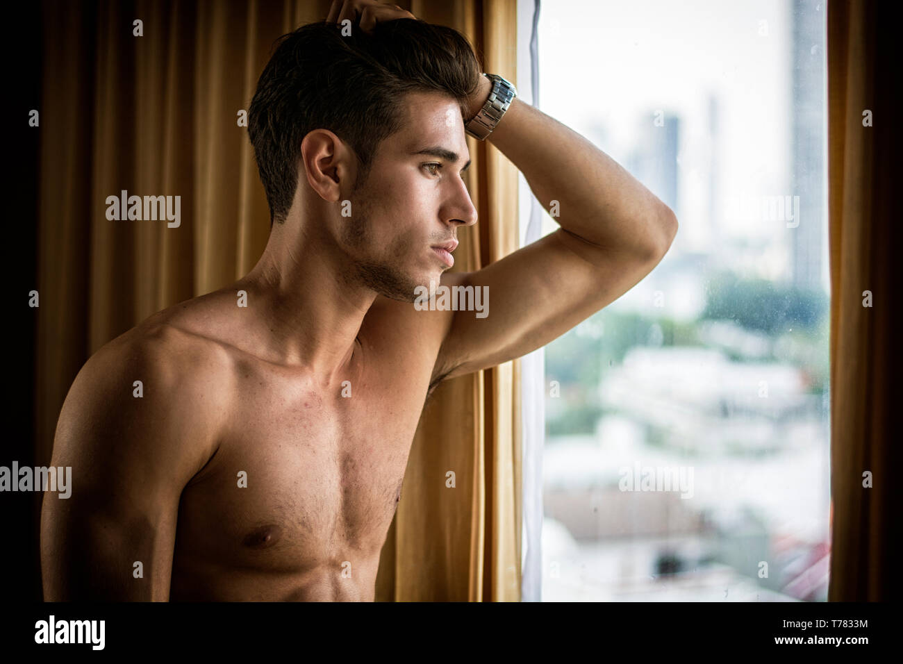Sexy handsome young man standing shirtless in his bedroom next to window curtains Stock Photo