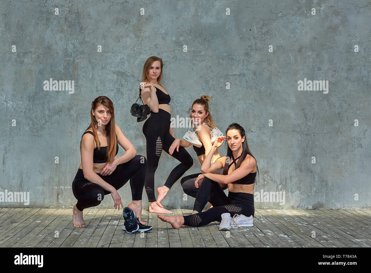 Group portrait of young sporty excited beautiful girls with exercise mats standing beside white wall laughing and talking together. Candid funny Stock Photo