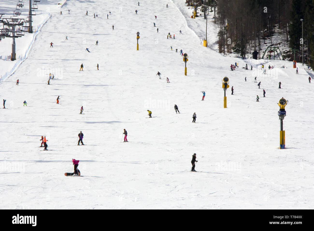Lots of skiers and snowboarders on the slope at ski resort - Stock Image