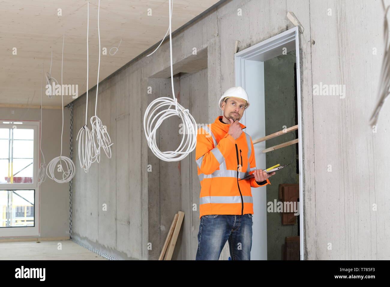 A Critical construction expert appraiser checking a constructin site - Stock Image