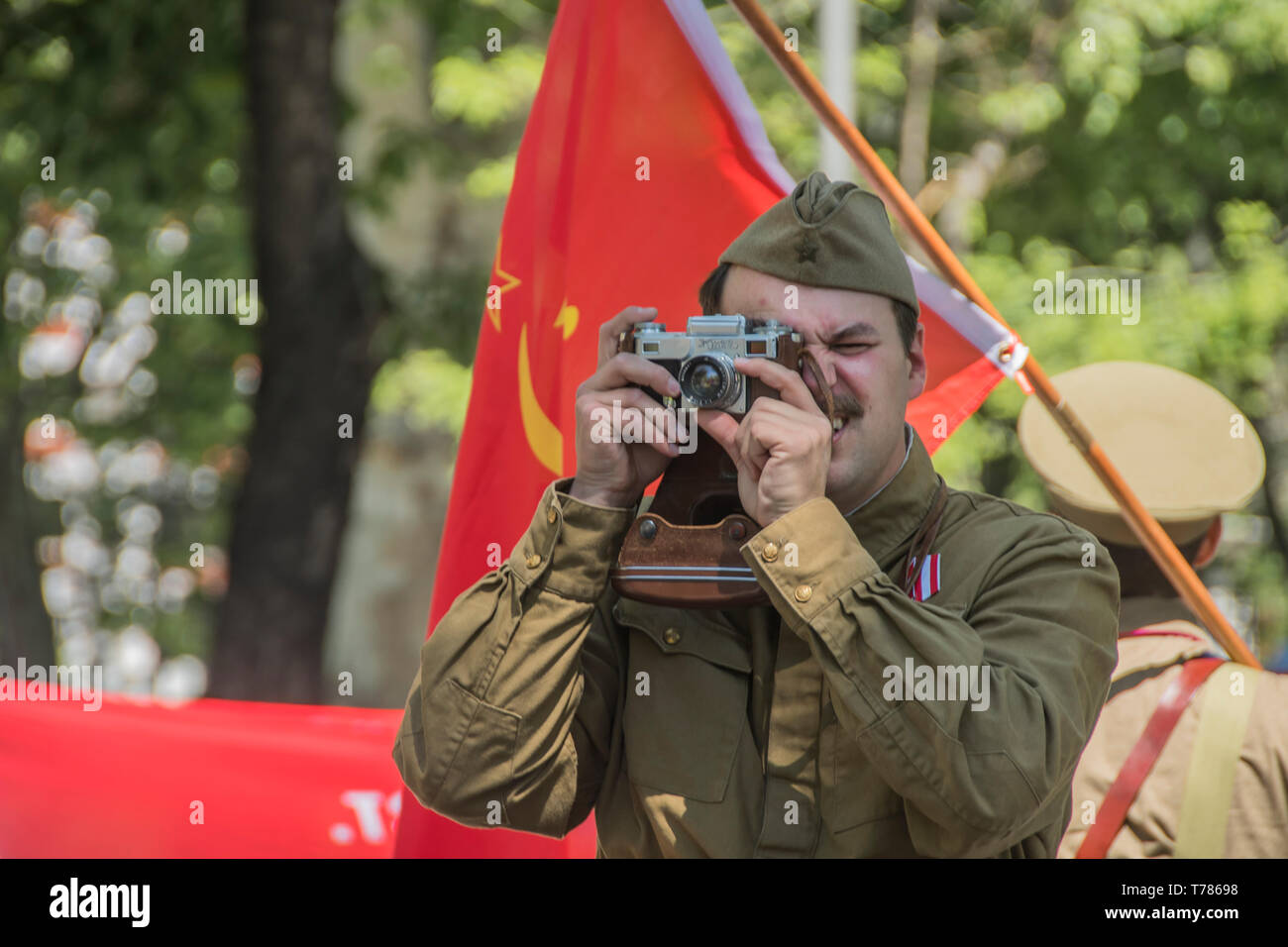 A man taking a picture with a Russian zenit camera in the celebration of the soviet union in its victory in world war II in Madrid, Spain. celebration - Stock Image