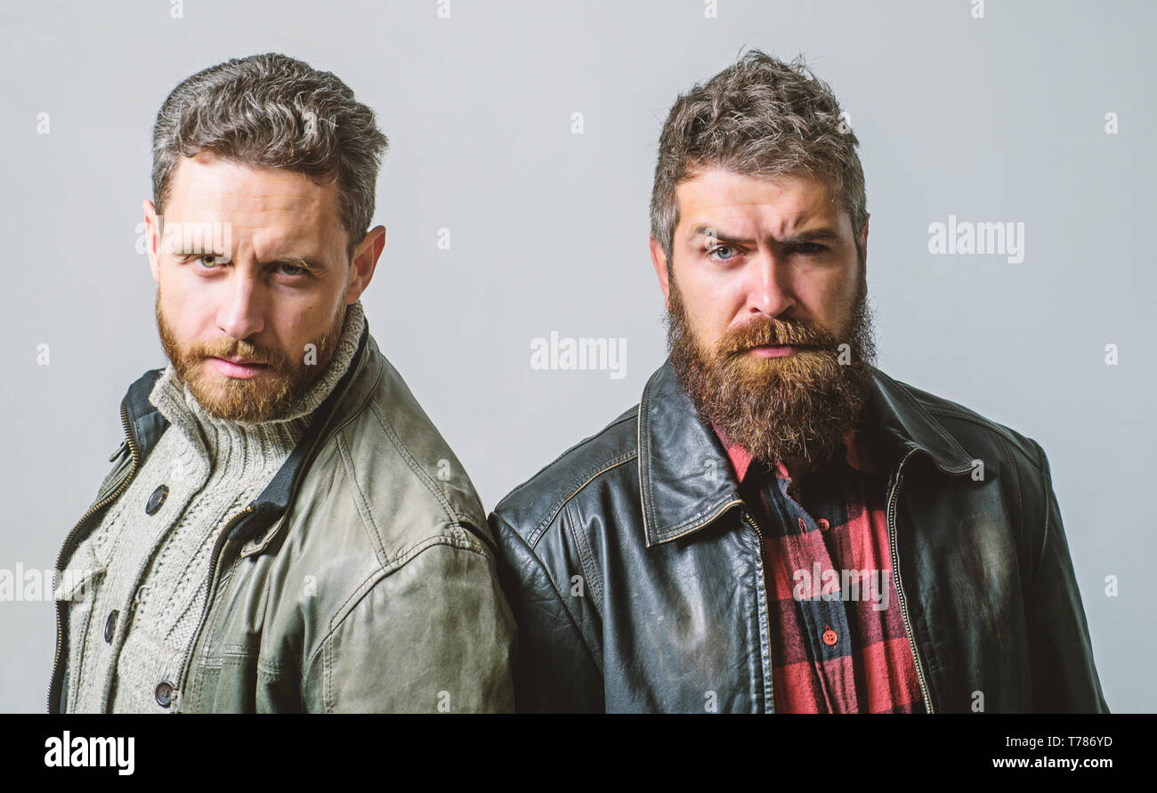 Men brutal bearded hipster. Handsome stylish and cool. Masculine and brutal friends. Bully team. Masculinity and brutality. Feel confident in brutal leather clothes. Brutal men wear leather jackets. - Stock Image