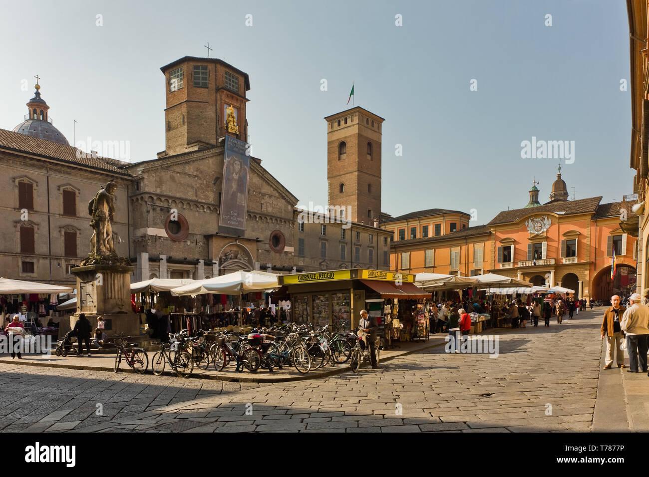 Reggio Emilia: Piazza Prampolini su cui si affacciano il Duomo, la Torre del Bordello  e il Palazzo del Comune. Bancarelle di mercato, edicola e bicic - Stock Image
