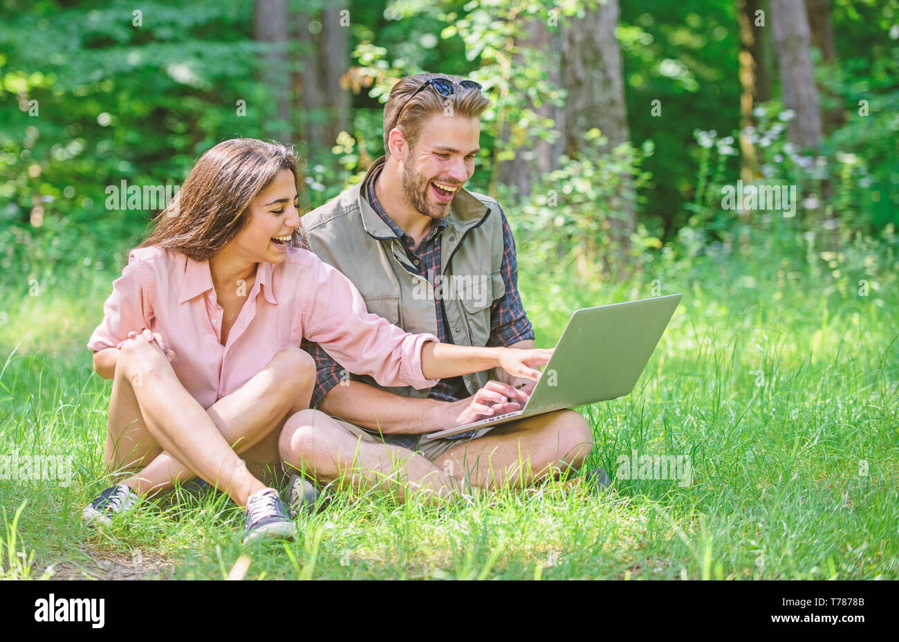 Modern technologies give opportunity to be online and work in any environment conditions. Man and girl looking at laptop screen. Freelance opportunity. Couple youth spend leisure outdoors with laptop. - Stock Image