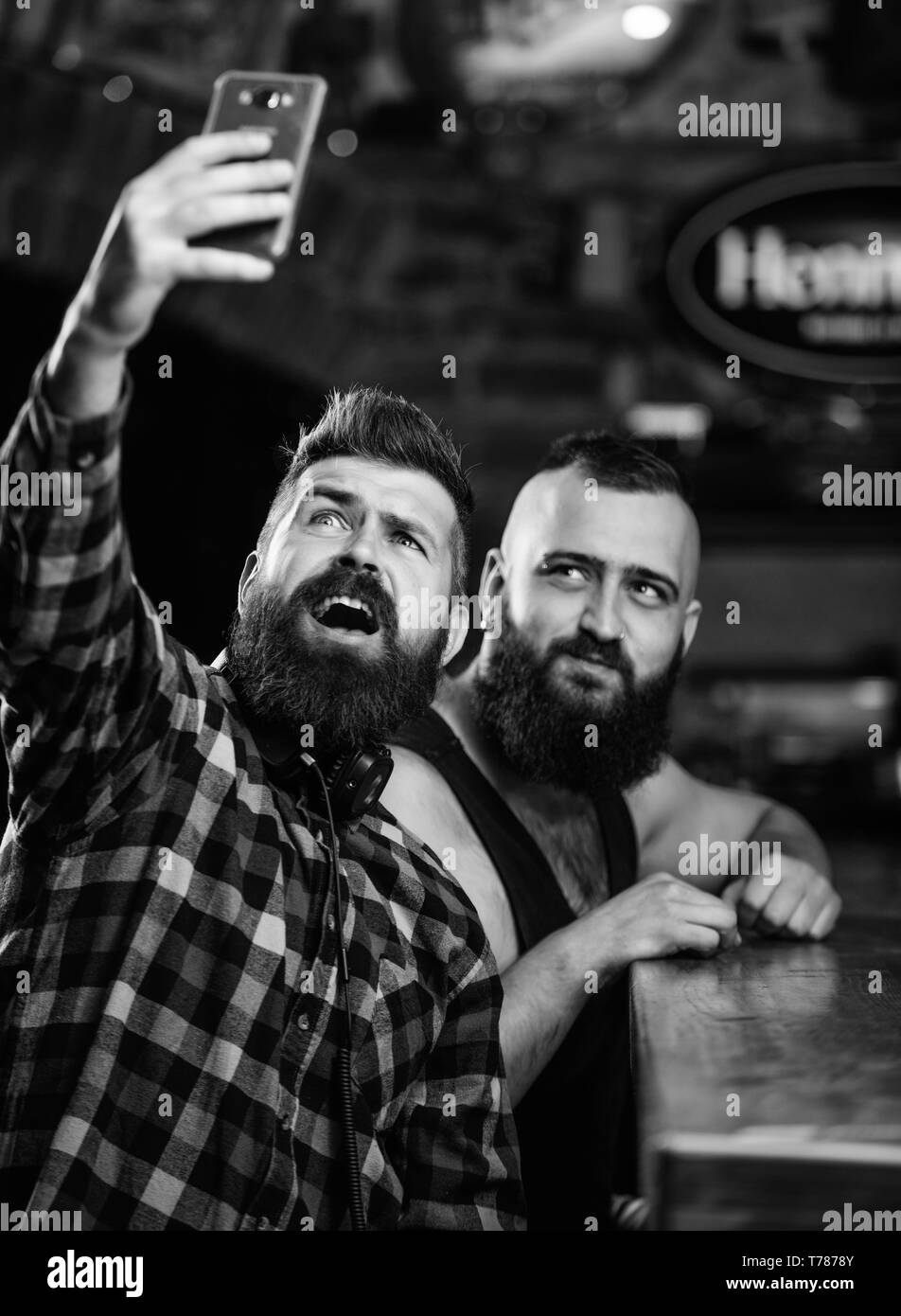 Man bearded hipster hold smartphone. Taking selfie concept. Send selfie to friends social networks. Man in bar drinking beer. Take selfie photo to remember great evening in pub. Online communication. - Stock Image