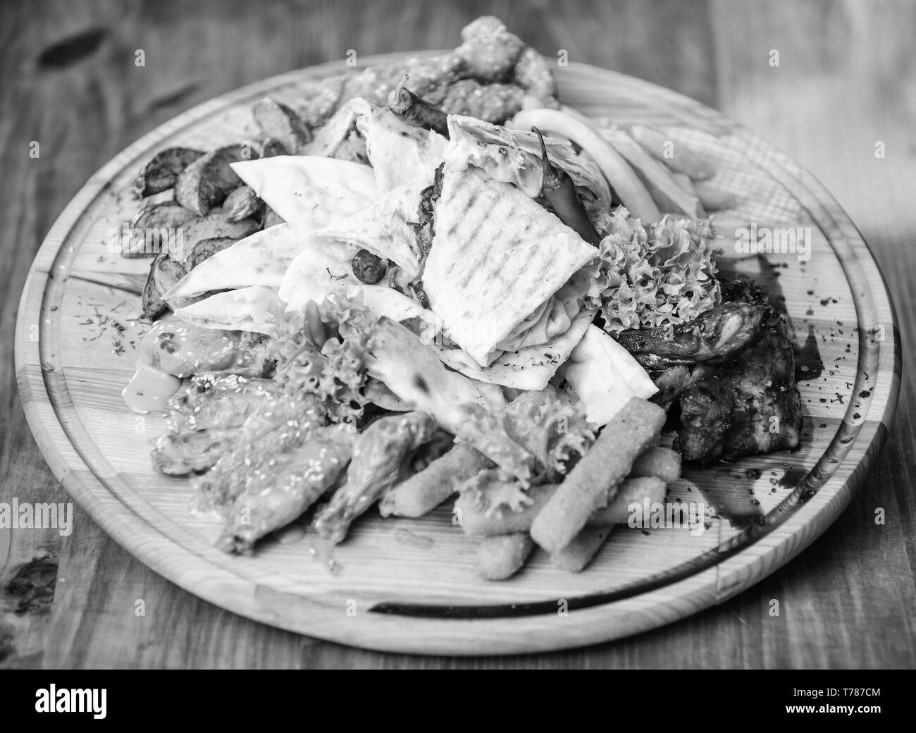 Meat snack for group friends. Tasty delicious snacks. Restaurant food. Snack for beer. Wooden board french fries fish sticks burrito and meat steak served with salad. Enjoy your meal. Pub menu snack. - Stock Image