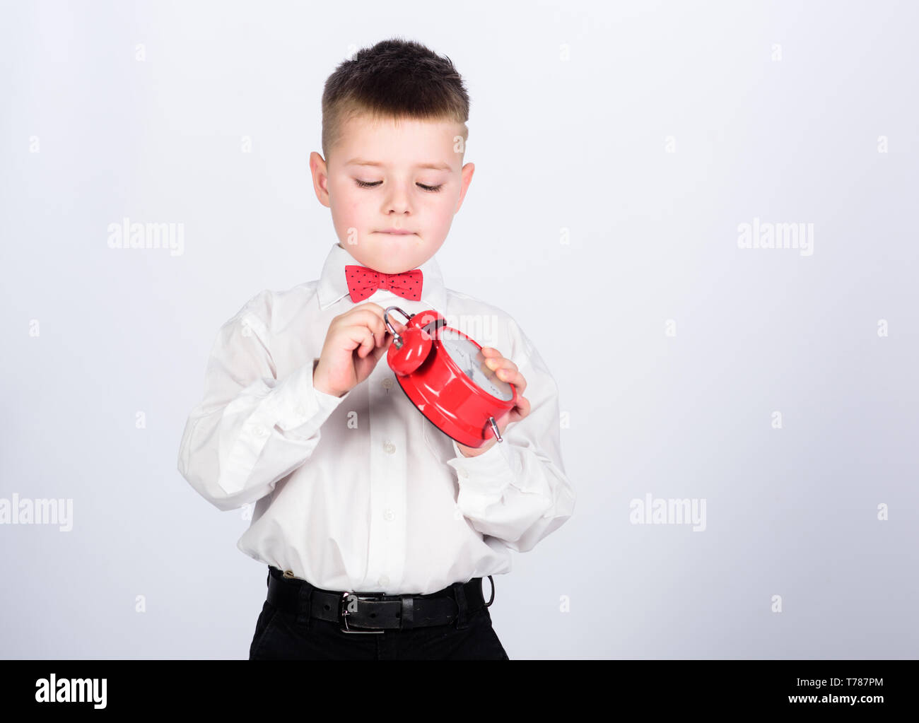 Set up alarm clock. Child little boy hold red clock. It is time. Morning routine. Schoolboy with alarm clock. Kid adorable boy white shirt red bow tie. Develop self discipline. Schedule and timing. - Stock Image
