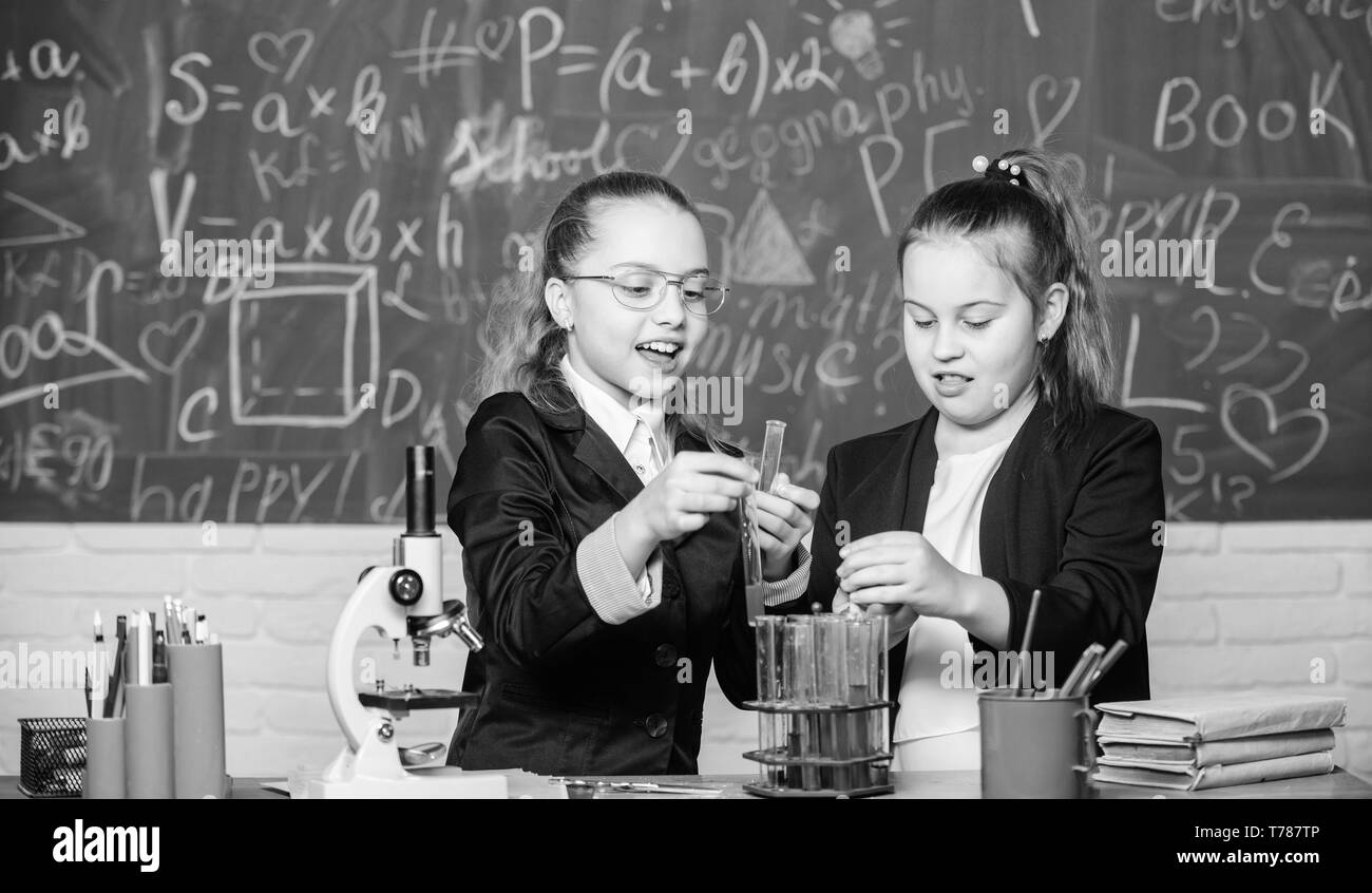 Safety measures for providing safe chemical reaction. Genius kids work on own chemical theory. Basic knowledge of chemistry. Pupils cute girls use test tubes with liquids. Chemical experiment concept. - Stock Image