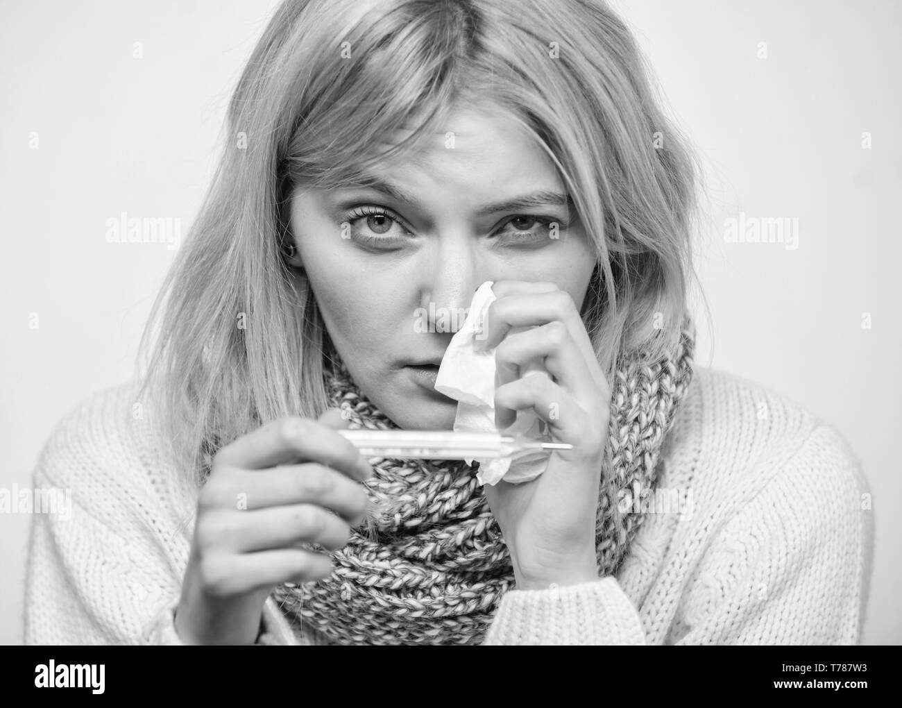 High temperature concept. Take temperature and assess symptoms. Measure temperature. Woman feels badly ill sneezing. Girl in scarf hold thermometer and tissue close up. Cold and flu remedies. - Stock Image