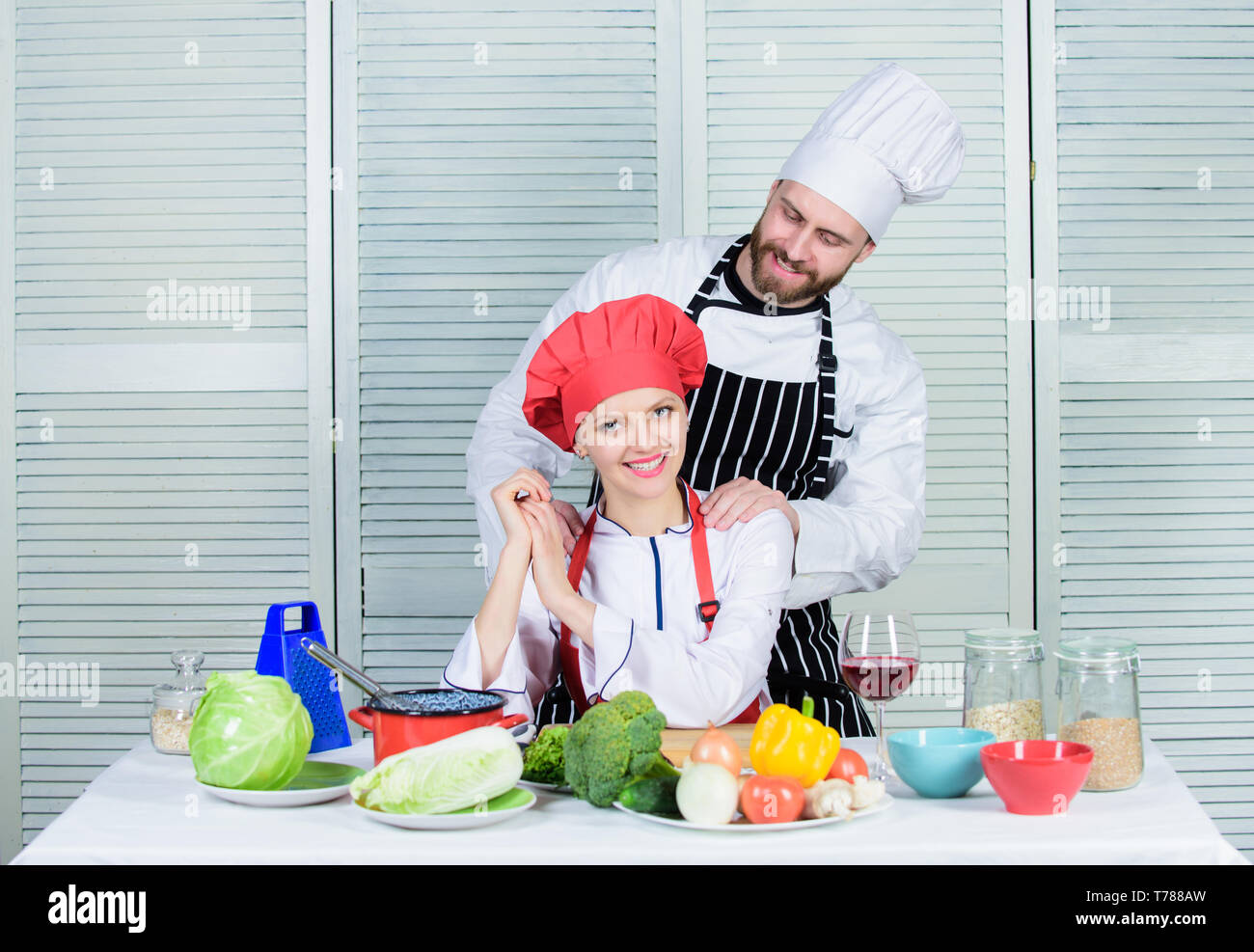 Woman and bearded man culinary partners. Ultimate cooking challenge. Couple compete in culinary arts. Reasons why couples cooking together. Cooking with your spouse can strengthen relationships. - Stock Image