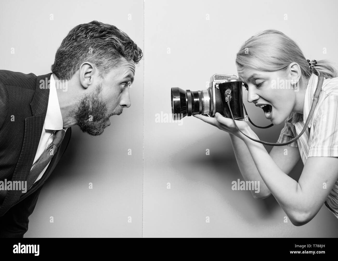 Emotions through photos. Businessman posing in front of female photographer. Pretty woman using professional camera. Photographer shooting male model in studio. Fashion shooting in photo studio. - Stock Image