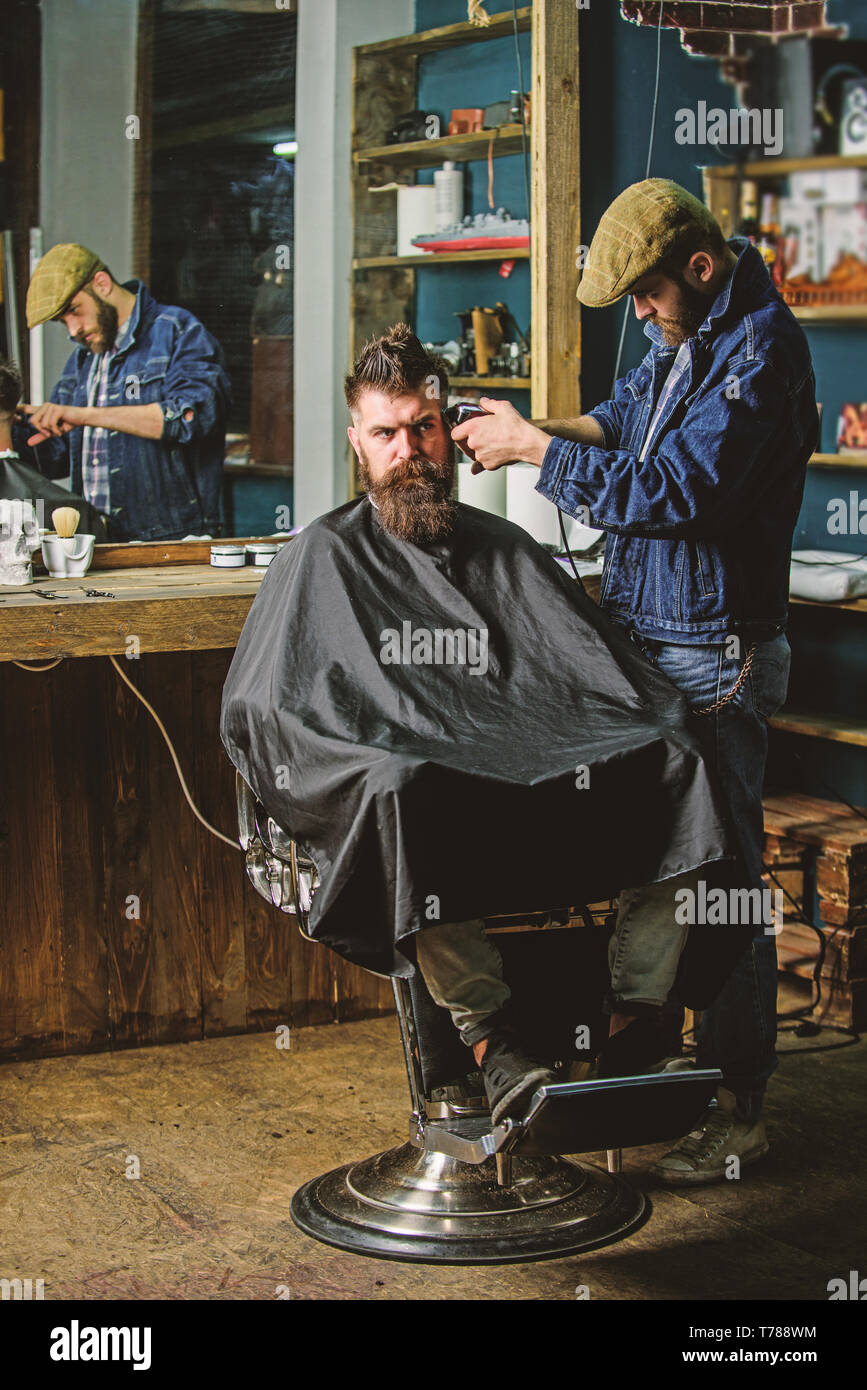 Hipster client getting haircut. Barber with clipper trimming hair on temple of client. Barber with hair clipper works on hairstyle for bearded man barbershop background. Hipster lifestyle concept. - Stock Image