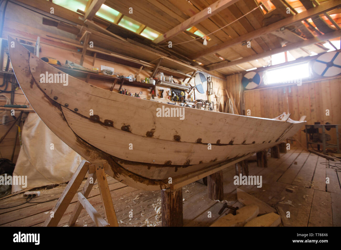 Handmade wooden boat in the barn , work tools on background - Stock Image