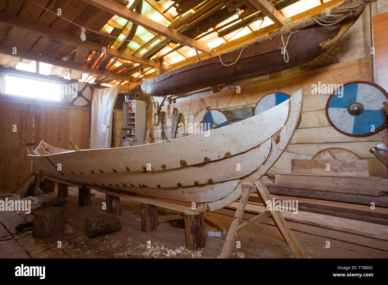 Handmade wooden boat in the barn , work tools and reenactor shields on background - Stock Image