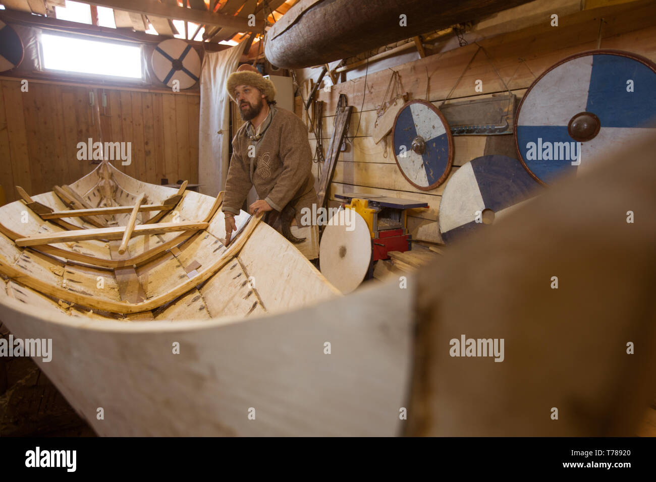 Handmade wooden boat in the barn and reenactor in medieval clothes - Stock Image