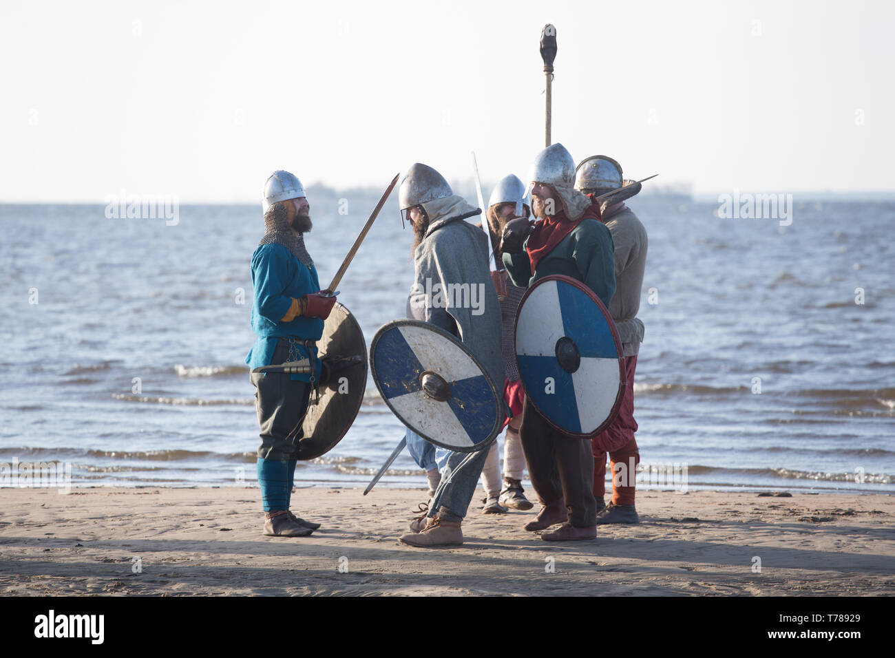 Slavic warriors reenactors with wearpons and shields getting ready for training outdoors at seaside - Stock Image