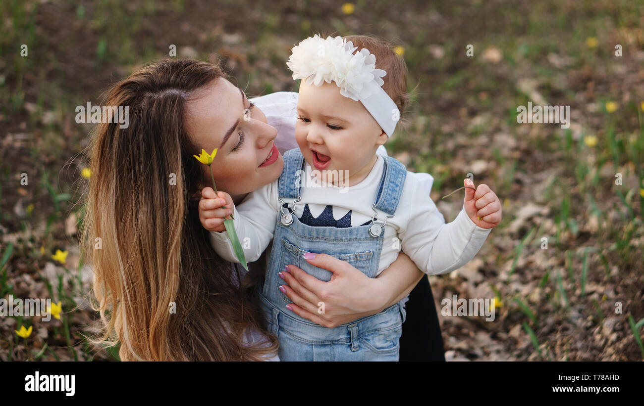 Family portrait close up mom hugs one year old daughter baby is holding flower in her hands and is enjoying walk in spring meadow family time