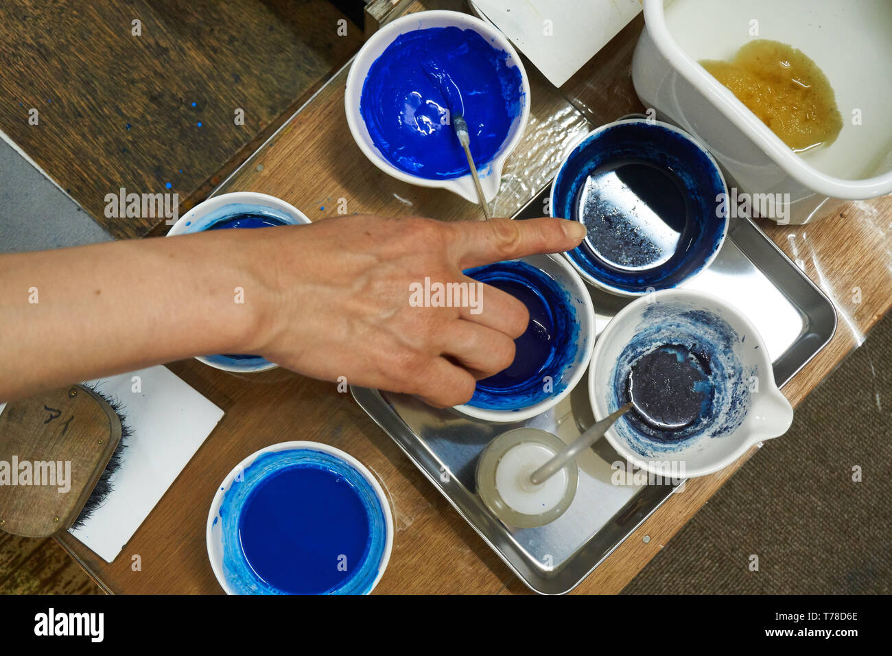 A Japanese woman woodblock printmaker points at her blue pigments arranged in cups with brushes on a table with other tools surrounding them. - Stock Image