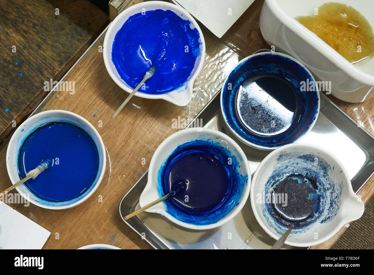 A Japanese woodblock printmaker's blue pigments arranged in cups with brushes on a table with other tools surrounding them. - Stock Image
