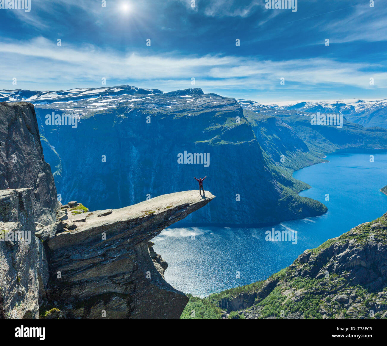 The summer sunshiny view of Trolltunga (famous The Troll's tongue Norvegian destination) and Ringedalsvatnet lake in Odda, Roldal, Norway. Man tourist - Stock Image